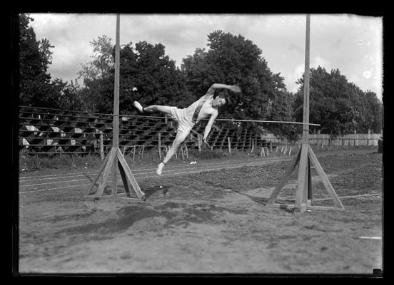 Track meet, high jump, only bleachers in background