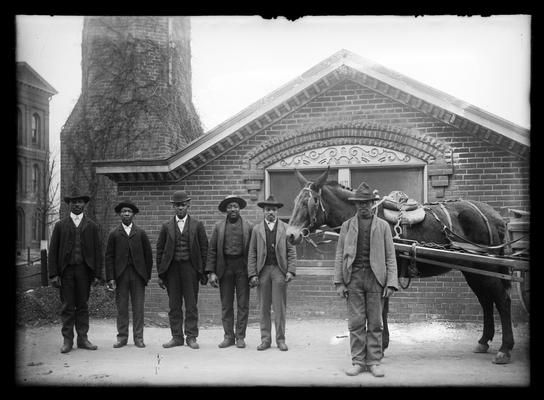 Six janitors and horse and wagon in front of heating plant                         We Are Seven