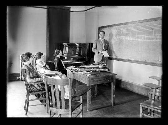 Class in music with Professor Lampert at blackboard, three women students, violin on the table