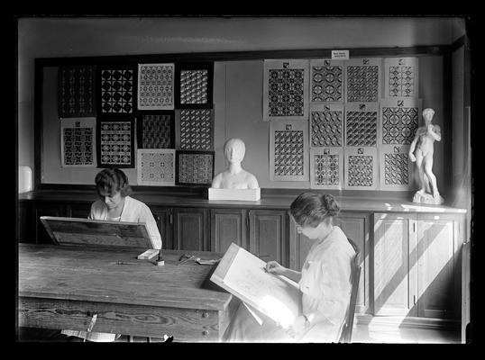 Two students sketching in an art class room, designs on wall in background, two pieces of sculpture on table