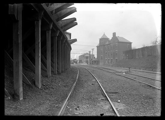 Train approaching, three story building on right, track curves around loading platform