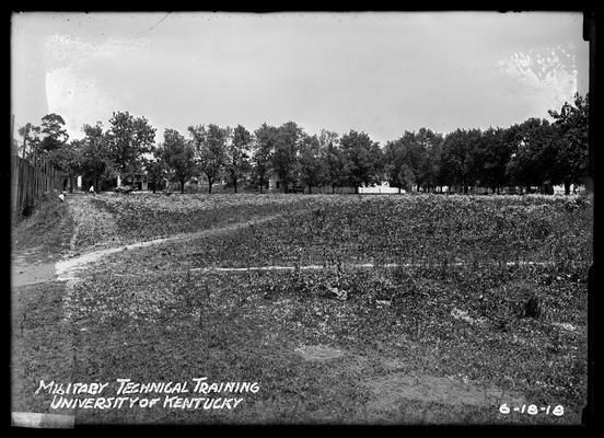 Fence to left, child leaning down, plowing in far left background