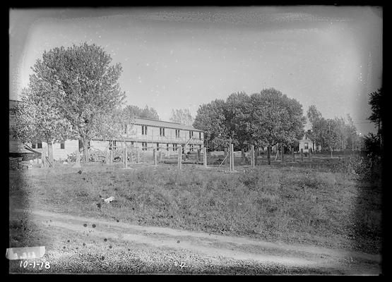 Barracks to left, posts for another, house in background