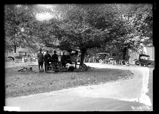 Auto shop, exterior, men under tree, cars and parts in background by armory