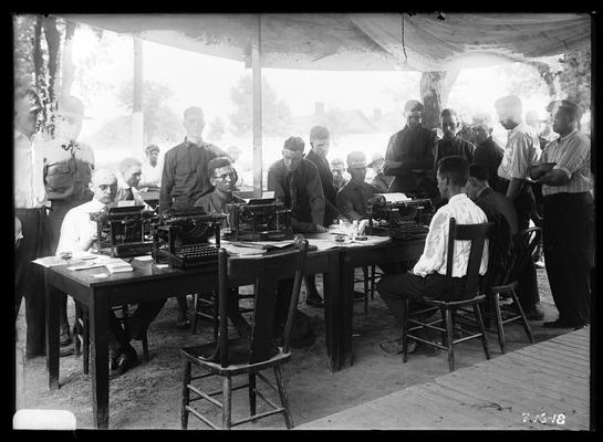 Several men at typewriters at table, other standing around