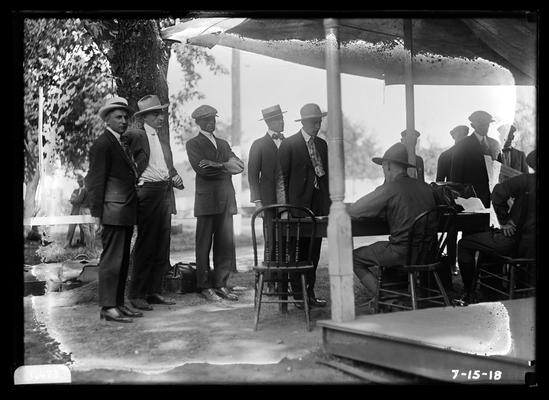 New arrivals, men with bags, others at table in front of building