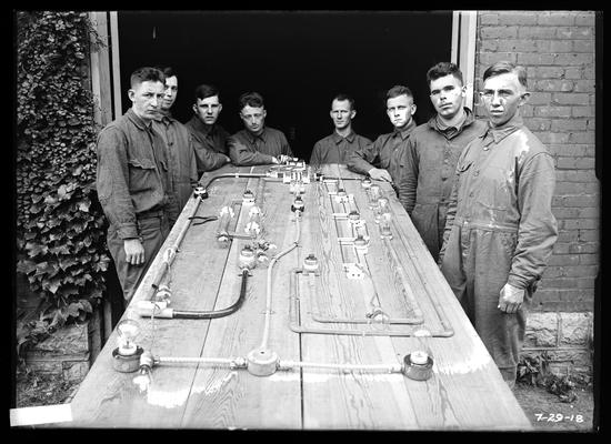 Wiring exercises on table, eight men, table has been brought outside