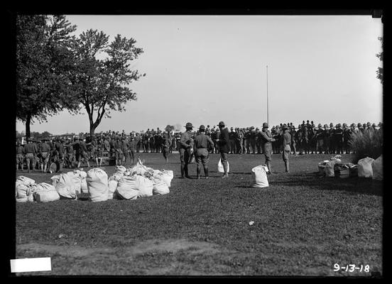 Breaking camp, duffel bags in foreground, men, empty flagpole