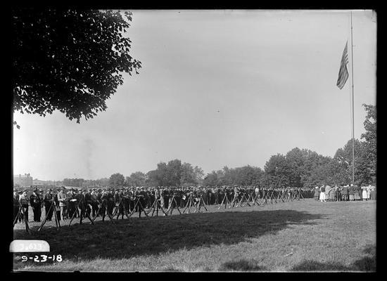 Memorial services, women around flag pole, men in formation, etc