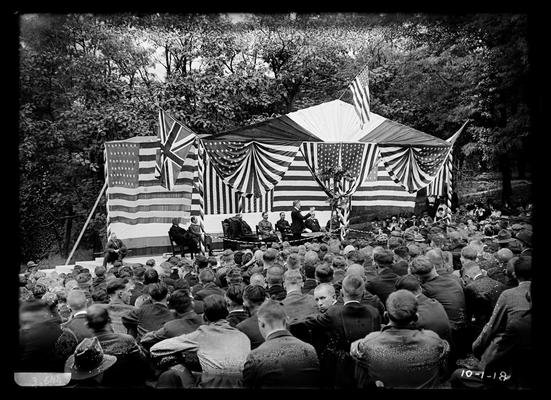 View of speakers on platform under tent, United States flag at top, British to left, at Railroad Memorial