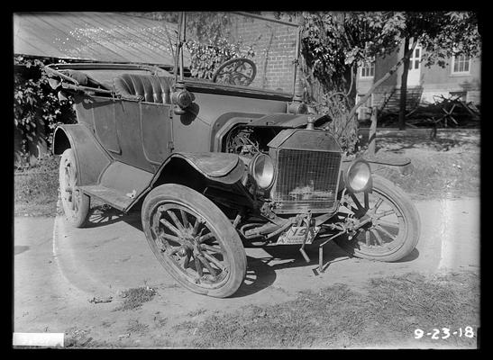 Ford which has been wrecked, United States of America Technical Training, University of Kentucky on license plate, house in right background