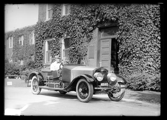 Open car with driver, in front of Mechanical Hall, 1924 license, possibly Charles H. Anderson