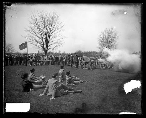 Notation                          Firing the cannon, April 1898, artillery unit with several cannon, mobile on wheels, five spectators seated in foreground