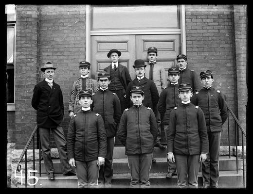 F. Paul Anderson, two men in civilian uniform, nine in cadet uniforms of three types