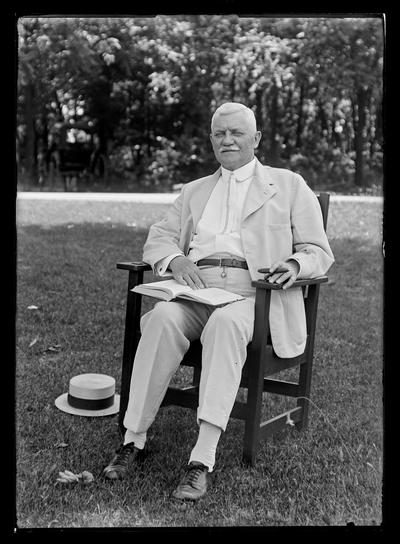 Professor M.A. Cassidy with book, cigar, in chair outside