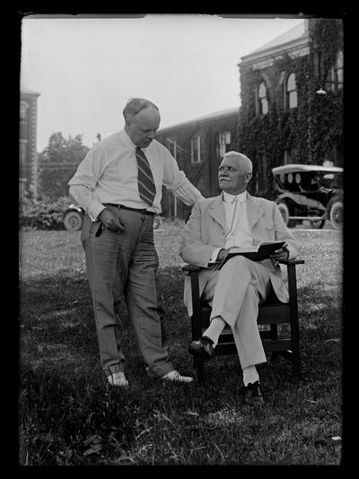 Professor M.A. Cassidy in chair with F. Paul Anderson standing Mechanical Hall in background