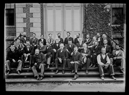 University of Kentucky faculty group, 1895-1896, seated, hats off, on steps of Administration Building (Main Building)