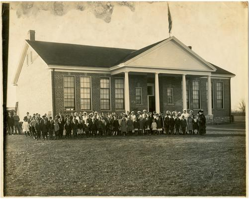 Group portrait of Athens students and Nannie Faulconer (1865?-1940) standing in front of the school. Handwritten on verso Type of School Building used in Fayette County Rural Schools. The Colonial suits the landscape of this particular County, Athens-Dist. No.18. Fayette County, Kentucky