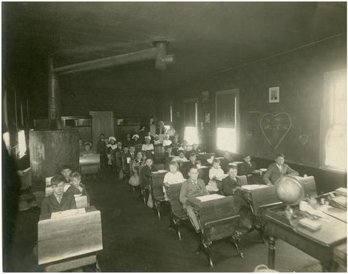 Cave Spring students sitting at their desks with Nannie Faulconer (1865?-1940) and teacher Rose Wurtele in the background. Handwriting on verso. (Four copies)