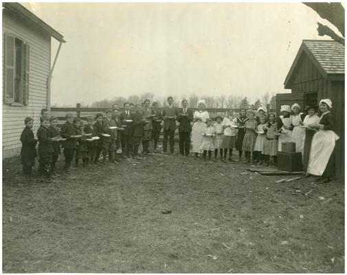 Cave Spring students being served lunch outside of the school house with Rose Wurtele and Nannie Faulconer (1865?-1940) (Two copies)