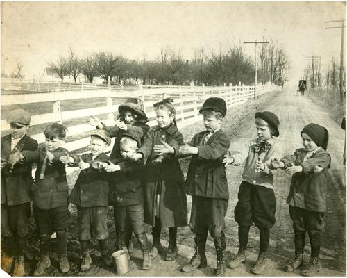 Group portrait of Greendale students posed with their hands outstretched. There is a horse and buggy in the background. Handwriting on verso. (Three copies)