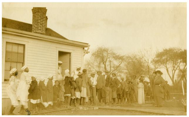 Maddoxtown students and Nannie Faulconer (1865?-1940) being served lunch outside the school house. Handwritten on verso, The penny lunch being served at Maddoxtown Colored School six miles from Lexington, Fayette County Kentucky. The majority of colored school in this county have regularly equipped kitchens. It is a windy day, Mrs. Nannie G. Faulconer, Superintendent inspecting