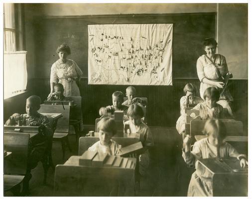 Picadome Montessori students working at their desks. Handwritten on oversized mat, Superintendent inspecting Montessori work in rural school Fayette County Kentucky. (Three copies, one Oversized)