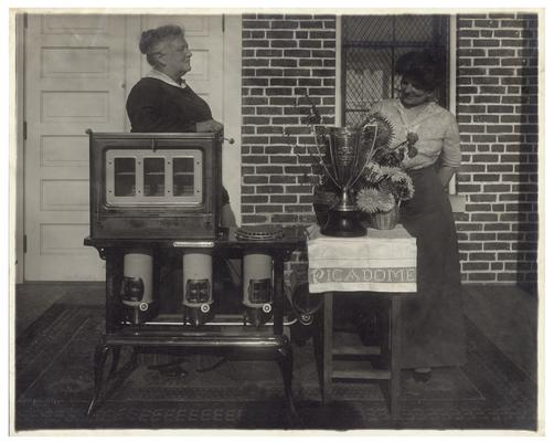 Portrait of Belle McCubbing and Nannie Faulconer (1865?-1940), posing with oven and trophy. Handwritten on verso, Silver Loving Cup and Blue Flame Oil stove won by Picadome rural school at the State Corn Show at Lexington, Fayette County Kentucky. The teacher Miss Belle McCubbing of Fayette County Ky. trained the class that won these prizes for the cheapest and best school lunch, and for the best soup made by the class after their own recipe