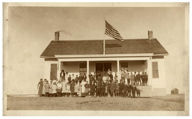Group portrait of Rose Hill students and Nannie Faulconer (1865?-1940) standing in front of the school house. Handwritten on verso,