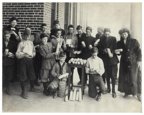 Group portrait of Picadome boys along with Nannie Faulconer (1865?-1940) and Margaret McCubbing examining ears of corn. Hand written on verso, Home and rural activities receive attention in Fayette County, Ky. In 1910. (Two copies)