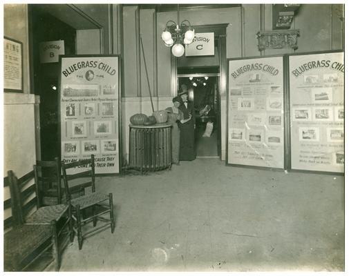 Portrait of Nannie Faulconer (1865?-1940) and Margaret P. McCubbing standing with three Bluegrass Child posters. Handwritten on verso, School Fair- Nannie Faulconer, Supt., M.P. McCubbing. (Two copies)