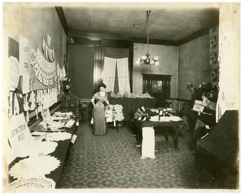 Portrait of Nannie Faulconer (1865?-1940) at the school fair with displays of students' work (A). Handwriting on verso. (Three copies, one in Oversize)