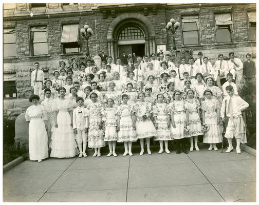 Group portrait of the graduating class of 1913 with Mrs. Nannie Faulconer (1865?-1940) at the Fayette County Court House. Handwritten on verso, ...graduating class of 1913 before the Fayette County Court House. These are all pupils of the Fayette County Grammar Schools. Supt. Nannie G. Faulconer. (Two copies)