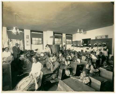 Group portrait of students sitting at their desks with Nannie Faulconer (1865?-1940) in the background