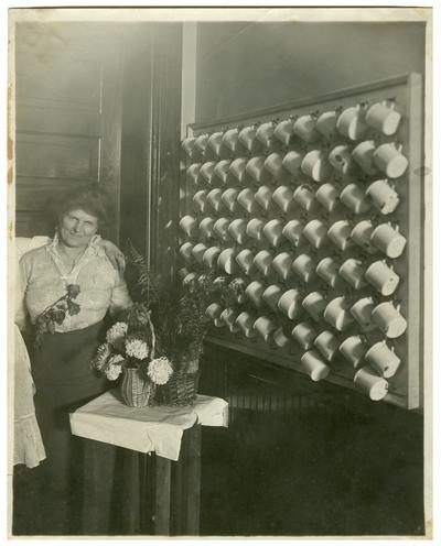 Portrait of Nannie Faulconer (1865?-1940) standing beside a wall of soup cups