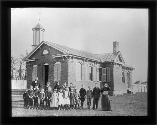 Students outside Little Picadome School with Miss Sara Drake, teacher, and County Superintendent M.A. Cassidy who coined the name