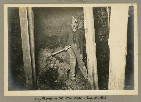 Title handwritten on photograph mounting: Log Found in No. 202 Mine