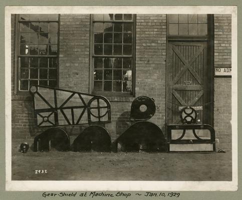 Title handwritten on photograph mounting: Gear Shield at Machine Shop