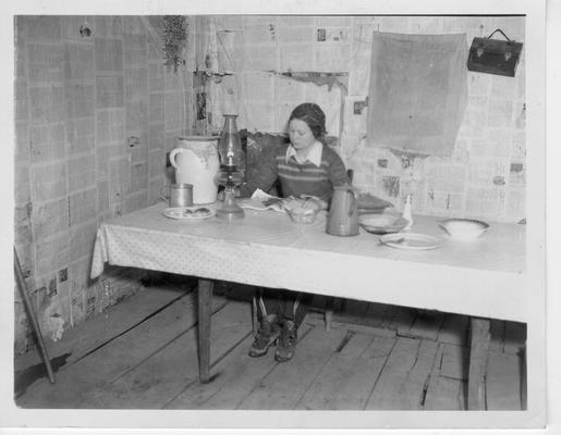 Interior of mountain cabin. Packhorse Library Carrier is seated at wooden table