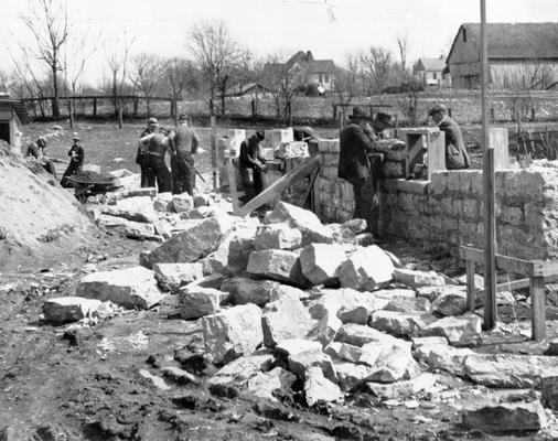 Project #2365 District 2: Construction of a municipal building, housing the city hall, fire station, and city jail in the City of Monticello, KY. The building is being constructed of native stone, quarried as part of the project. The view shows workmen laying the stone walls. Photographed March 25, 1936