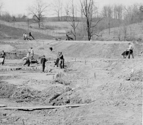 Project #2288 District 5: Construction of eleven fish rearing pools and game hatchery for the State Game and Fish Commission of Kentucky. Site of the project adjoins the Bellefonte Country Club near Ashland, KY. View shows construction of curved earth dam. Photographed March 25, 1936