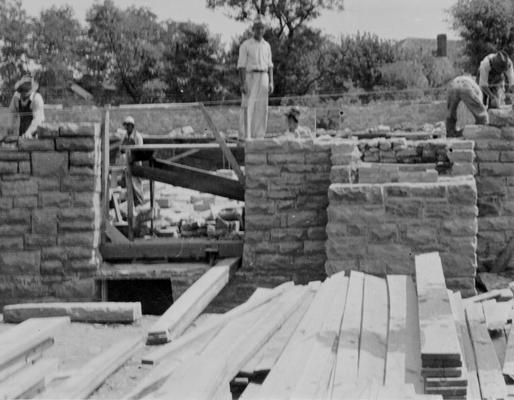 Project #1303 District 4: Gymnasium Building, Sharpsburg, KY. Construction of a combination gymnasium-auditorium building, of native limestone for the Sharpsburg Independent School in Bath County. The photograph, taken July 22, 1936, is an exterior view, showing stone masons laying wall