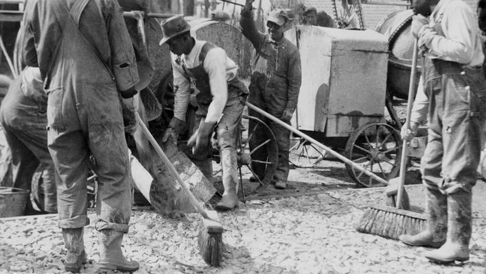 Project #486 District 1: Workmen spreading grout over the rock base during construction of cement bound macadam streets in Princeton, KY. View of the work was photographed March 14, 1936