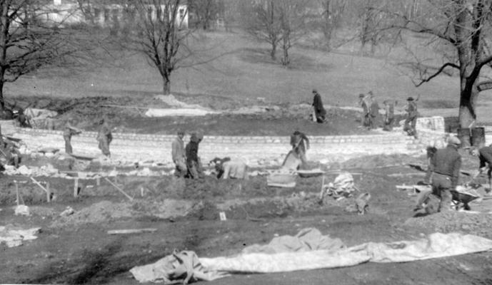 Project #1175 District 4: WPA Project #1175 is providing an outdoor amphitheatre on the campus of Eastern Kentucky State Teachers College in Richmond, KY. It will consist of 16 grass terraces with native stone risers, an earth stage and a small pool. Construction of amphitheatre photographed February 28, 1936