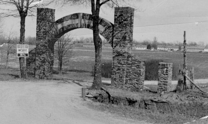 Project #9962 District 1: Blue and Gray State Park Project. Construction of transient camp at Blue and Gray State Park in Elkton, KY. Transients at the camp are employed to make improvements in the park. Scene photographed April 15, 1936, shows the entrance gate to the park and panorama of the camp buildings constructed on the project
