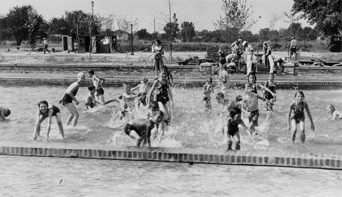 Project #120 District 6: Children waging a water battle in the wading pool at the Cypress and Algonquin Parkway Playground, Louisville, KY. This 13-acre playground was developed under Project #120. The view was photographed July 22, 1936