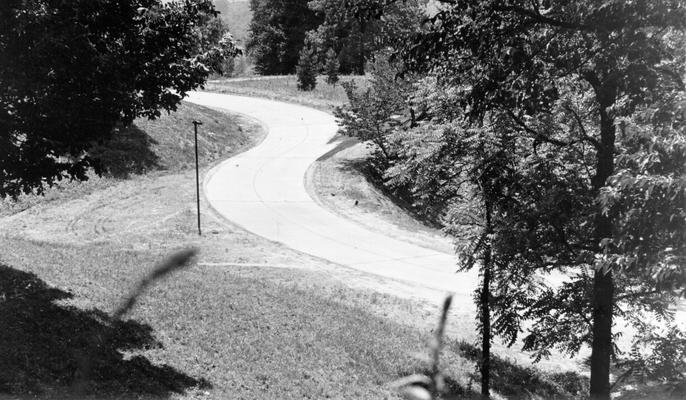 Project #1037 District 6: The construction of a concrete road on the property of Waverly Hills Sanitorium was completed under Unit #6-56-43 of Master Project #1037. The road extends from the Dixie Highway to the main entrance of the hospital. View shows completed section of front entrance road to the hospital, photographed June 8, 1936