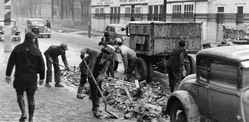 1937 Flood. Clean-up work in Louisville, KY. WPA workers cleaning up debris from 22nd Street, just north of Broadway. Note the water line on the buildings across the street. View photographed February 8, 1937