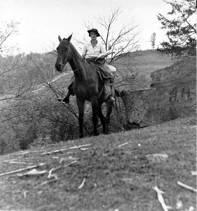 Project #2323 District 4: The establishment and operation of a pack horse library in Owsley County, District 4, is Project #2323. Four pack horse librarians in this county rode 564 miles last month with saddle bags filled with books and magazines, which were distributed in rural and isolated sections of the county. The books and magazines are later collected in a similar manner for redistribution. A Pack Horse Librarian returning over the mountain side for a new supply of books. View photographed October 15, 1936