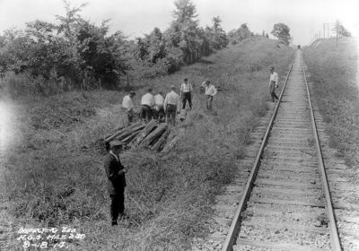 Men inspecting railroad ties, stretch of track